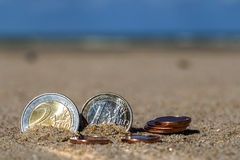 Business coins at holiday in the sand on the beach, North Sea Stock Image