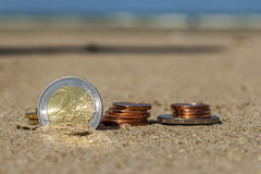 Business coins at holiday in the sand on the beach, North Sea Stock Photos