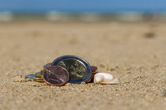 Business coins at holiday in the sand on the beach, North Sea Royalty Free Stock Images