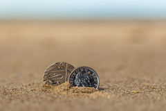 Business coins at holiday in the sand on the beach, North Sea Stock Photography