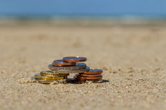 Business coins at holiday in the sand on the beach, North Sea Stock Images