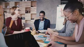 Business collaboration in modern loft office. Young happy multiethnic start-up colleagues smiling, brainstorming 4K. Diverse milllennial creative employees stock footage
