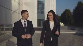 Business people while working near office building. Business colleague - young man executive and attractive businesswoman outdoors during break on warm summer stock footage