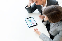 Business colleagues analysing a graph. Overhead view of two business colleagues, a men and woman, analysing a statistical business graph on a tablet computer as stock photos