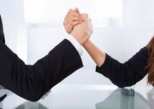 Business colleagues arm wrestling Stock Photos