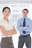 Business colleagues with arms crossed in office Stock Image
