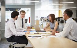 Business colleagues brainstorming in an open plan office royalty free stock photo