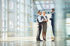 Business Colleagues Chatting at Coffee Break. Group of modern business people chatting during coffee break standing in sunlit glass hall of office building royalty free stock photography