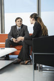 Business Colleagues Communicating In Office Lobby Royalty Free Stock Photos