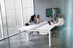 Business colleagues in conference meeting room during presentation. Business colleagues in modern conference meeting room during presentation royalty free stock images