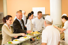 Business colleagues cook serve lunch canteen food. Cook serve meals business women take lunch in cafeteria Stock Photos