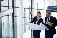 Business colleagues discussing with blueprint in corridor Stock Images