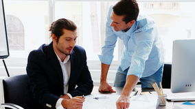 Business colleagues discussing on blueprint stock footage