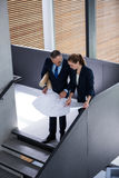 Business colleagues discussing on blueprint while standing on staircase Stock Photography