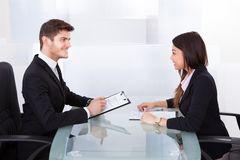 Business Colleagues Discussing At Desk Royalty Free Stock Image