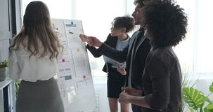 Business people discussing with reports on whiteboard at office. Business colleagues discussing with financial reports on whiteboard at office conference stock footage