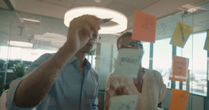 Business colleagues discussing new ideas. Business colleagues brainstorming together at a glass wall wth adhesive notes. Businesswoman with male coworker stock video