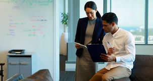 Business colleagues discussing over digital tablet and clipboard. In office stock footage