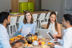 Business colleagues discussing over digital tablet while having breakfast Stock Images