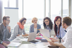 Business colleagues discussing over photographs at conference table in creative office Stock Photos