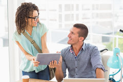 Business colleagues discussing over a tablet Royalty Free Stock Image
