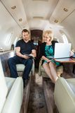 Business Colleagues Discussing On Private Jet Stock Image