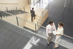 Business Colleagues Discussing By Railing In Office Stock Images