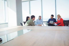 Business colleagues discussing while sitting against window at office. Business colleagues discussing while sitting on chairs against window at office Royalty Free Stock Photos