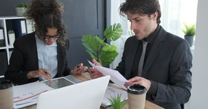 Business colleagues doing paperwork at office. Businessmen and businesswoman doing paperwork at office desk stock video