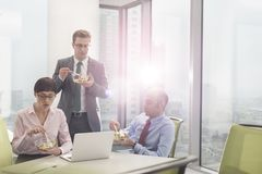 Business colleagues eating lunch in boardroom during meeting at office royalty free stock images