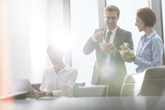 Business colleagues eating lunch in boardroom during meeting at office stock photo