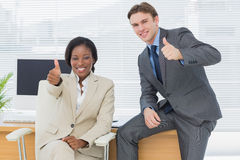 Business colleagues gesturing thumbs up in office Royalty Free Stock Photography
