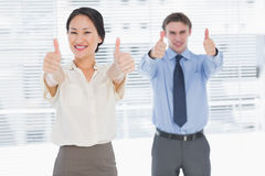 Business colleagues gesturing thumbs up in office Royalty Free Stock Image