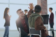 Business colleagues giving each other high five. The concept of teamwork stock image