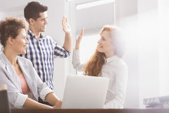 Business colleagues giving high five. Successful business colleagues giving high five at desk in office royalty free stock photos