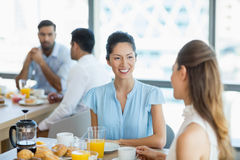 Business colleagues having breakfast together in office cafeteria Stock Photography