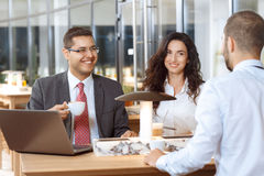 Business colleagues having friendly conversation. Three business colleagues having a friendly conversation during coffee break Stock Photography