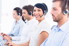 Business colleagues with headsets in a row Royalty Free Stock Photo