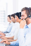 Business colleagues with headsets in a row Stock Image
