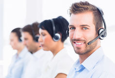 Business colleagues with headsets in a row Royalty Free Stock Photography