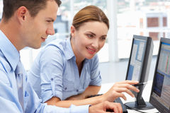 Business Colleagues helping each other on computer