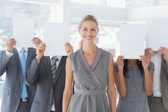 Business colleagues hiding their face with paper Royalty Free Stock Photography