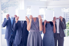 Business colleagues hiding their face with paper Stock Images