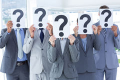 Business colleagues hiding their face with question mark sign Stock Image