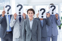 Business colleagues hiding their face with question mark sign Stock Photography