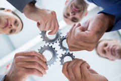 Business colleagues holding cog Royalty Free Stock Photos