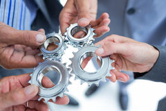 Business colleagues holding cog Stock Image