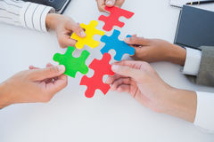 Business colleagues holding piece of puzzle Royalty Free Stock Photo