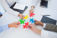 Business colleagues holding piece of puzzle Stock Photography