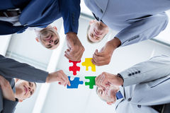 Business colleagues holding piece of puzzle Stock Photo
